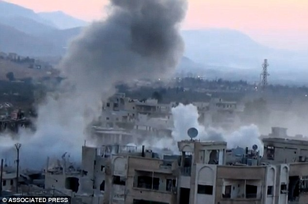 Smoke rises from buildings due to heavy artillery shelling in Barzeh, a district of Damascus, Syria, today