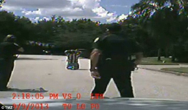 Officers approach Zimmerman, one with his gun drawn, as they prepare to handcuff him