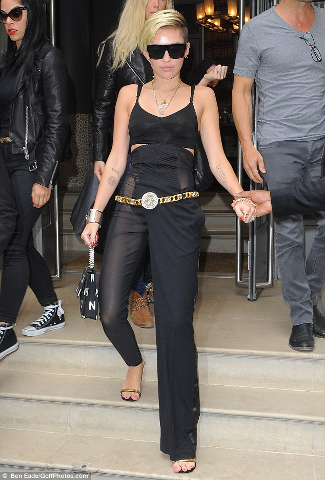 Miley Cyrus leaves her London hotel wearing a pair of bizarre flared and skinny trousers on Wednesday