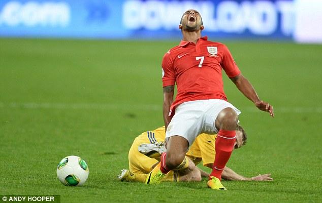 Tough night: Theo Walcott is hacked down by Ukraine captain Oleksandr Kucher