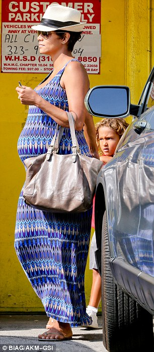 No hiding it: For their day of shopping, the Academy Award winner showed off her belly and pregnancy curves in a tight long blue patterned dress