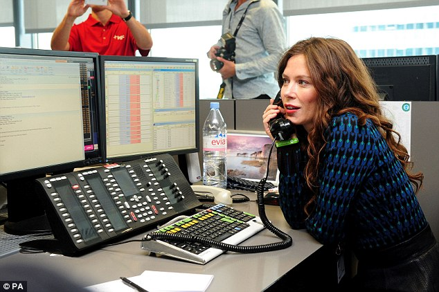 On call: Anna Friel talks to a potential donator during the charity event as a star-struck broker takes her picture in the background