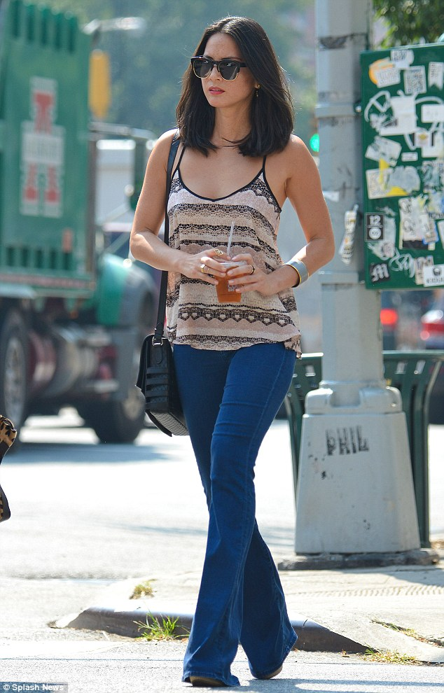Out and about: Olivia Munn appeared to be wearing the same pair of flared jeans when she ventured out in New York City earlier that day, shortly before meeting Joel at their hotel
