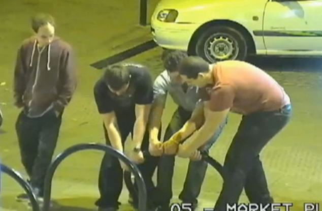 All together! The group of lads abandon their takeaways to try and pull back the severely bent bike rack