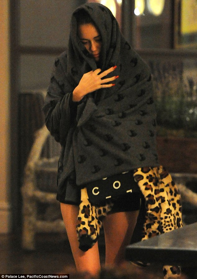 Under cover: Miley Cyrus covered her head with a blanket as she left her hotel in London on Thursday