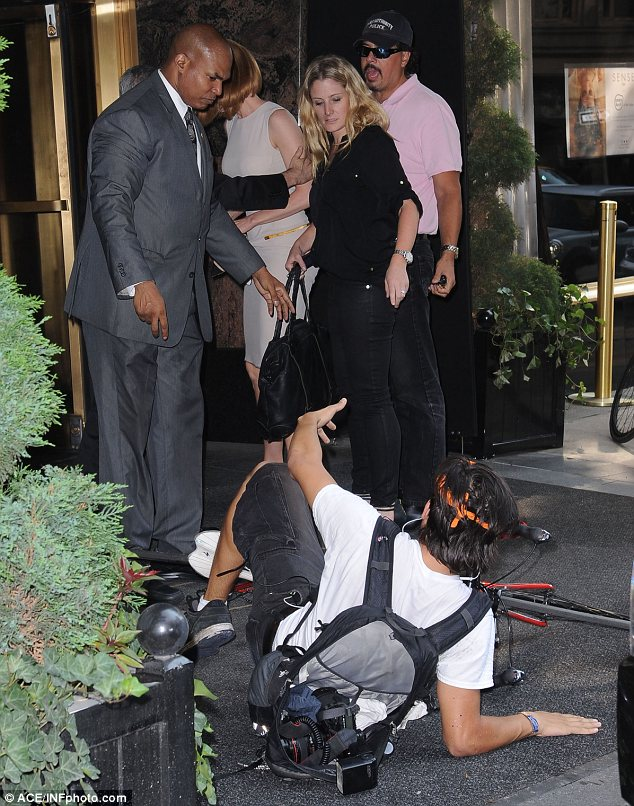 In trouble: A security guard wore a stern face as he talked to the paparazzo, who had his equipment in a rucksack