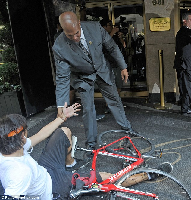 Off the sidewalk: As Nicole made her way inside, the bicycle-riding photographer got a helping hand up