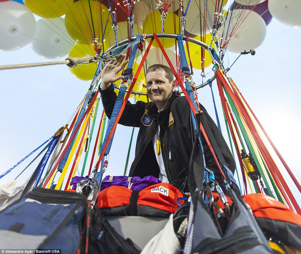 Bon voyage: Jonathan Trappe waves from the lifeboat which hangs from the balloons ahead of taking off from Caribou, Maine