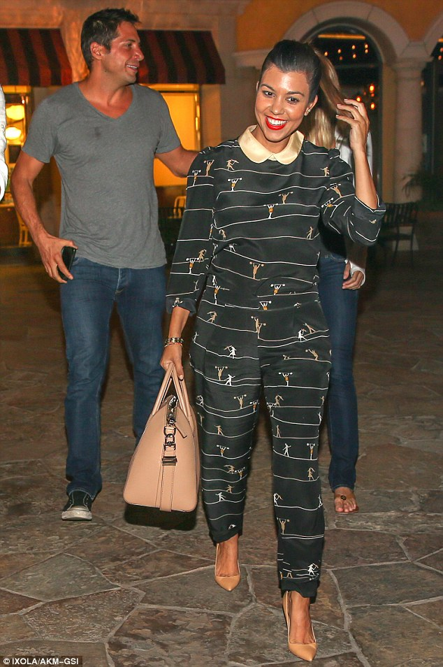 Taking a weight off her mind: Kourtney Kardashian steps out in a jumpsuit printed with weightlifters for a date night with Scott Disick