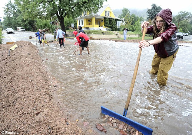 Street sweepers: Residents shovel debris to form a protective dike in a neighborhood of Boulder