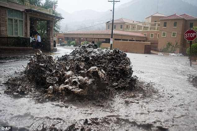 Geysers of sewage: A Sewer in Manitou Springs is overwhelmed by rainfall yesterday, gurgling the overflow of water