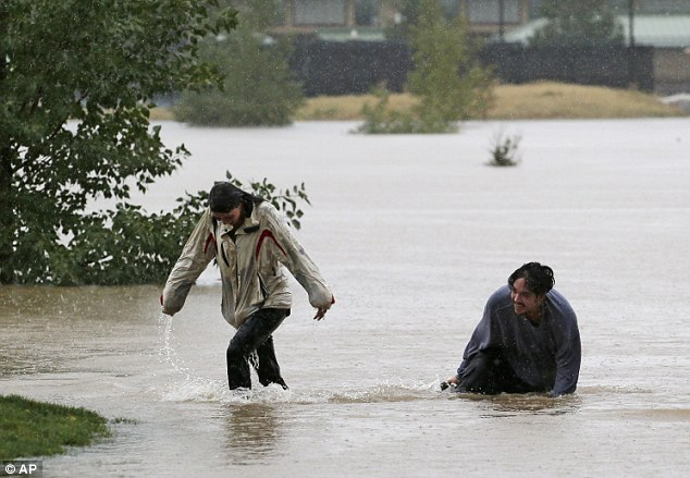 Pop-up pool: A couple play in the flooded Utah Park in Aurora, Colorado yesterday