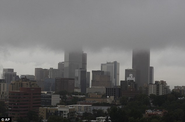 Ominous: Clouds cover the Denver skyline early this morning. It continues to rain in the area