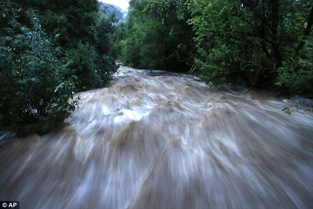 Out of control: The heavy rainfalls have turned Boulder Creek into a raging river with enough power to wash out roads