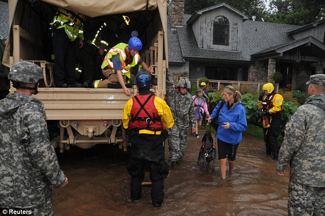 Aid: Colorado National Guardsmen help relocate a family trapped at their heavily-flooded home