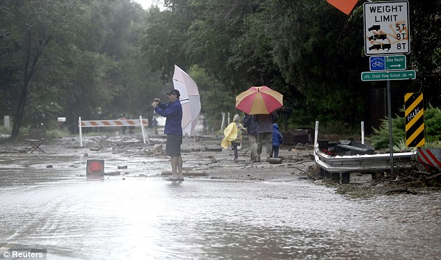 Exploring: Umbrella-toting residents take pictures of the damage the flooding had on a street in Boulder on Friday