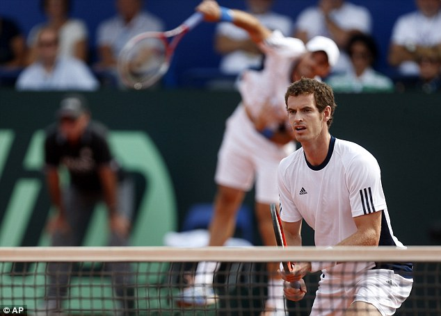 Full focus: Andy Murray stands at the net as Colin Fleming serves during the victory over Ivan Dodig and Mate Pavic
