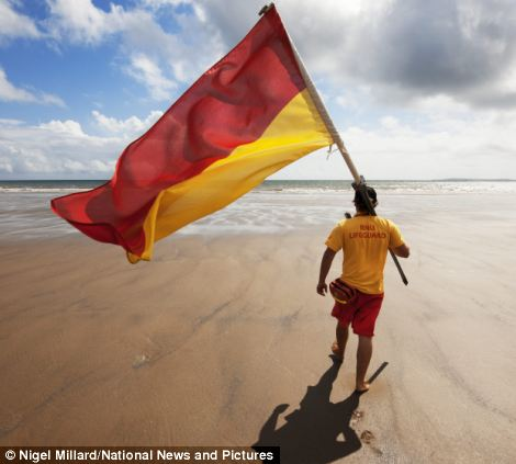 In the morning at Amroth, Pembrokeshire, lifeguard Ben Ablitt begins his day's work by setting out the safe swim flags