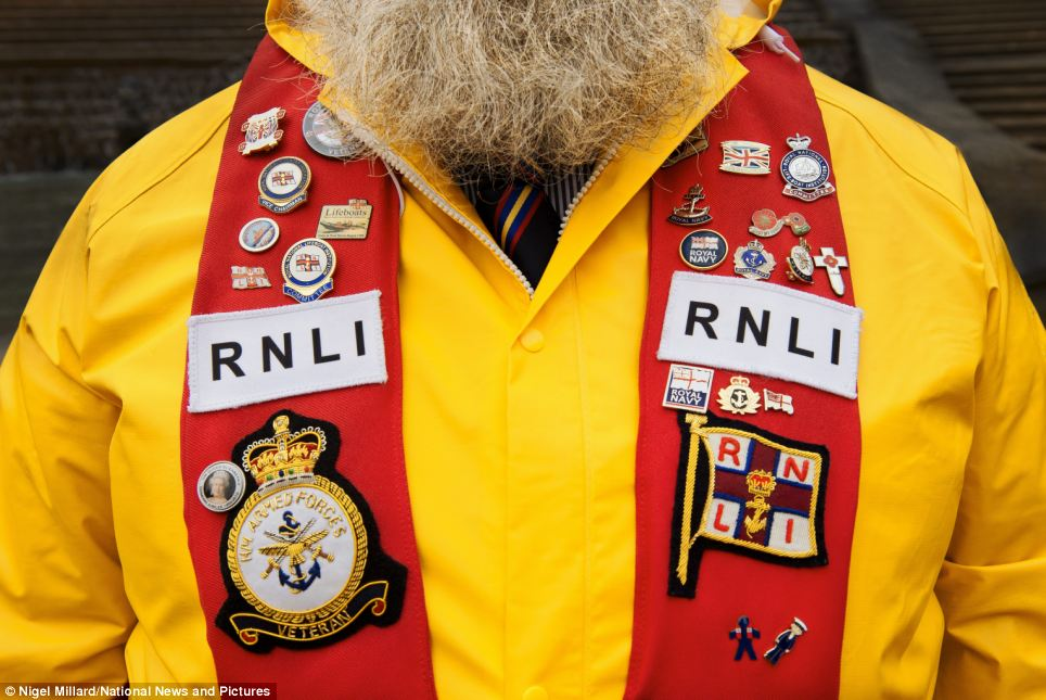 Long-standing volunteers are clad in badges on their yellow jackets