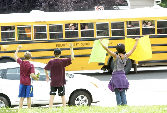 Rescued: Families cheer as a bus carrying several Fireside Elementary 5th graders who were trapped at Camp-Calwood arrive to school in Louisville, Colorado on September 14, 2013