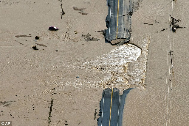A section of highway is washed out by flooding along the South Platte River in Weld County, Colorado near Greeley, Saturday, Sept. 14, 2013