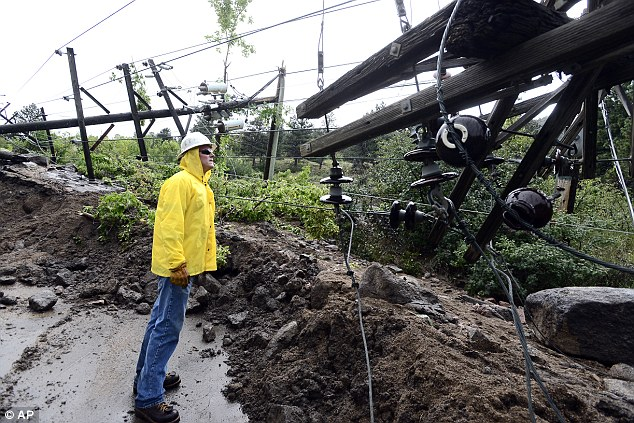 Justin Slyter with Par Electrical Contractors looks over fallen power poles in a office complex on Arapahoe Avenue next to Eben G Fine Park in Boulder on Saturday Sept, 14, 2013