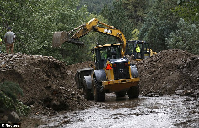 Access: Heavy equipment is used to try to clear debris from a road covered in 20ft banks of mud