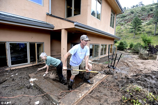 Relief: Brian Montgomery helps his mother Barbara Yanari to clean up the mud in her flooded basement on Saturday, Sept. 14, on Olde Stage Road in Boulder, Colorado