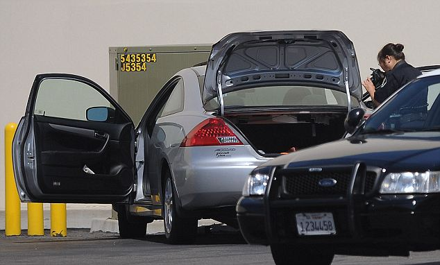 Crime scene investigators photograph a car believed to be driven by a women who allegedly tried to commit suicide by ramming it into a utility box behind a Costa Mesa shopping center. Her children were found dead in the Hampton Inn Suites in Santa Ana