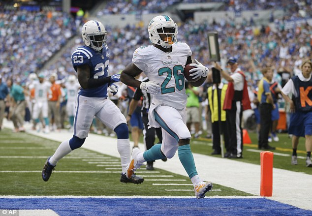 Score: Miami Dolphins' Lamar Miller (26) goes in for a 10-yard touchdown run