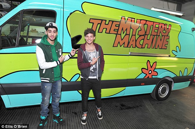 Zayn Malik and Louis Tomlinson stand beside their tour bus, The Mystery Machine