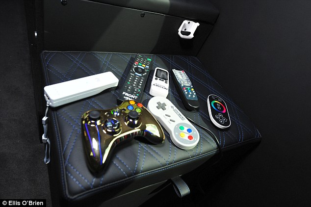 An array of remote controls and games consoles litter one of the leather seats