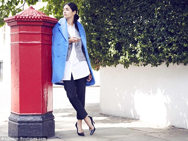 Cool coat draped over the shoulders with capris and a crisp shirt in blue and monochrome