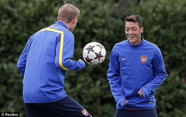 German love: Mertesacker and Ozil play some keepie-uppies on the training ground