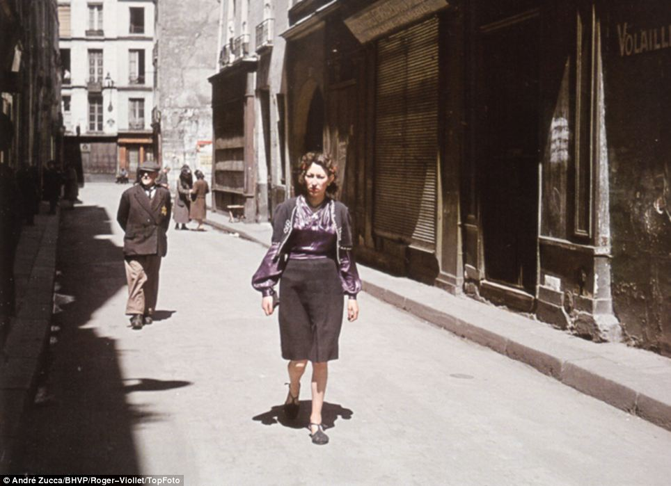 Real life under the Nazis: A woman walks a Parisian backstreet, in front of an older gentleman who is marked with the Star of David insignia that Jews were forced to wear