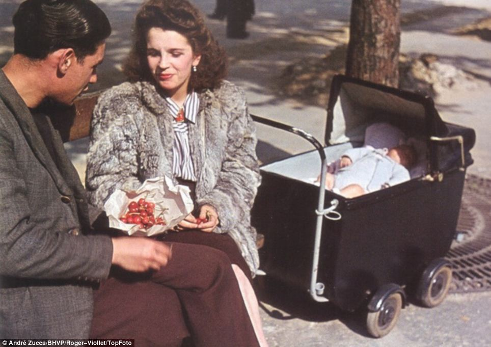 Shielded from war: A young family, including a man of usual conscription age, sit in the sunshine eating grapes