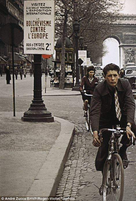 Grim-faced Parisian commuters cycle past another poster for the Europe Against Bolshevism exhibition