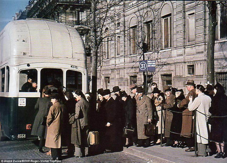 So did the buses run on time? Parisian commuters queue to board a bus on a chilly early morning under the Nazi yoke
