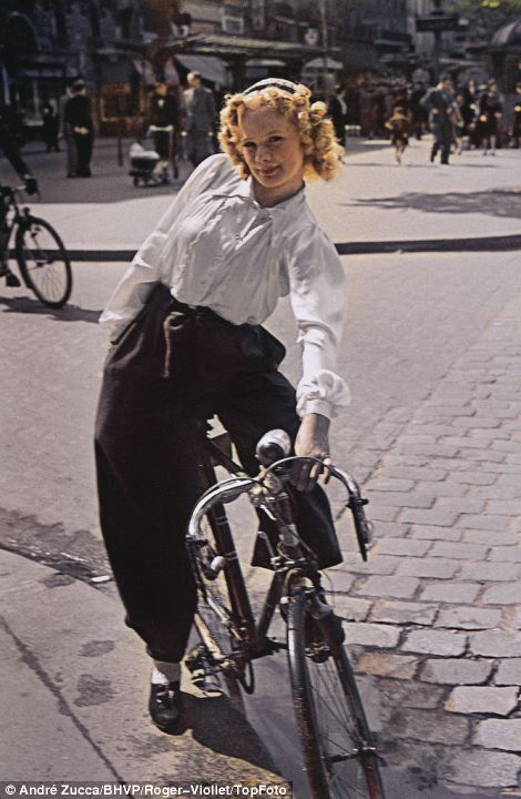 A pretty young woman poses on her bicycle