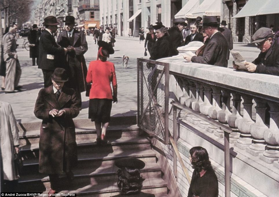 Life goes on: Parisians go about their business, walking down into a subway. The majority of Zucca's images show Paris as a thriving, lively city