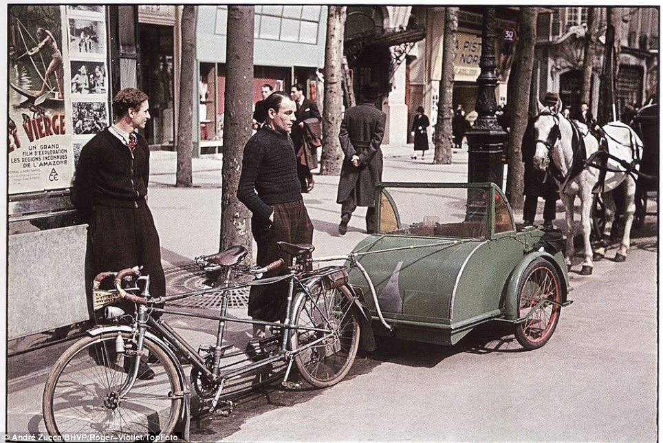 Ingenious contraption: Two fashionably dressed young men stand by a tandem bicycle towing a carriage of sorts