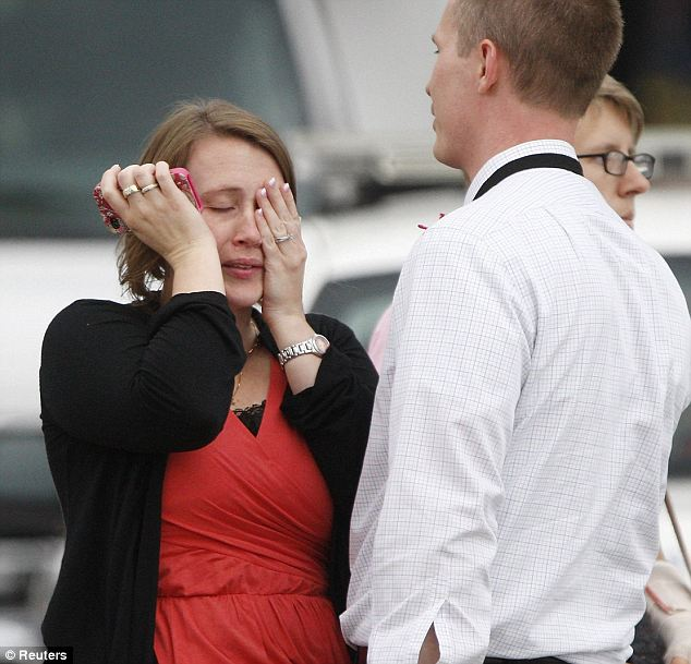 Tragedy hits DC: Following the shooting at the Navy Yard Monday morning, a woman (left) is reunited with her husband. All of the 3,000 people- mostly civilians- who work in the facility were ordered to remain inside