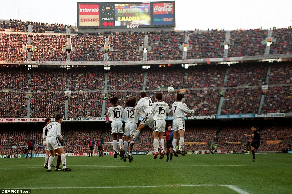Barcelona's Figo curls in a free kick against Real Madrid