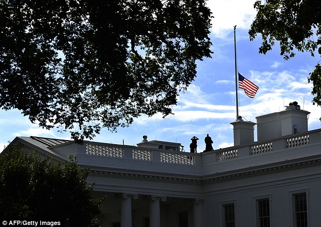 Members of the US Secret Service man their position on the roof of the White House as the national flag flies half-mast on September 17, 2013 a day after a deadly Navy Yard shooting in Washington, DC