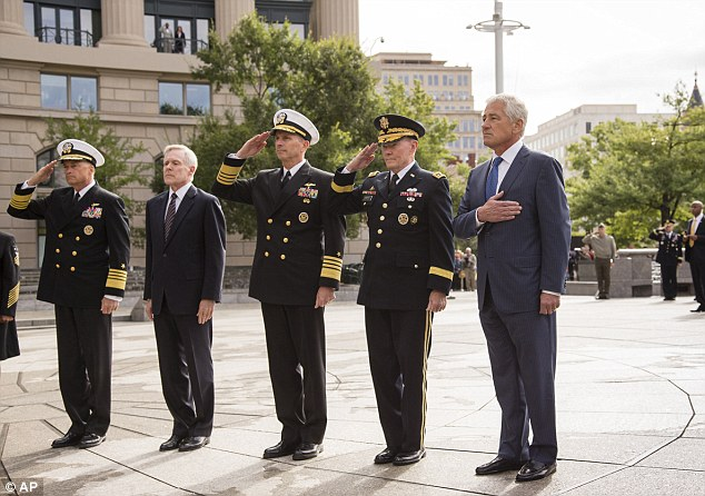 Salute: Defense Secretary Chuck Hagel, right, leads a delegation at the Navy Memorial in Washington to remember the victims of Monday's deadly shooting at the Washington Navy Yard on Tuesday