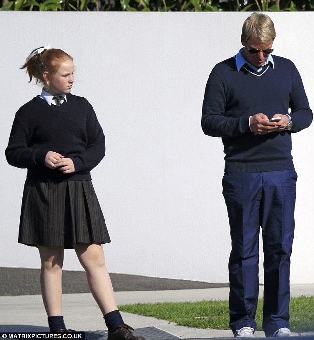 Preoccupied: Shane was seen on his phone while he stood beside his daughter Summer on Tuesday
