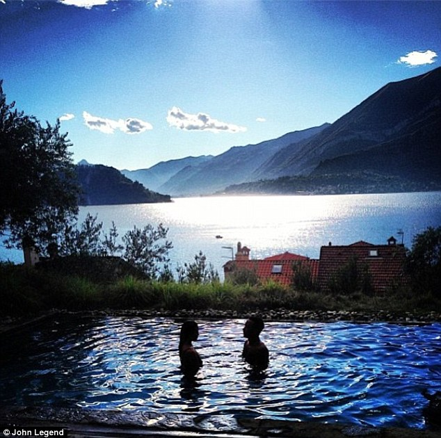 Stunning: John also shared a snap of their honeymoon, showing the couple taking a sunset dip in a private pool against the picturesque backdrop of a lake and mountains