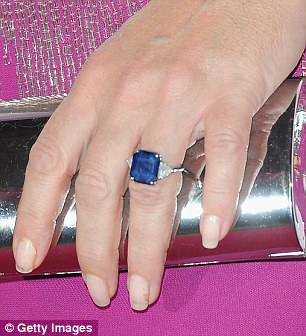 Disappearing acts: Hurley's diamond and sapphire engagement ring (seen right) was noticeably absent from her left hand