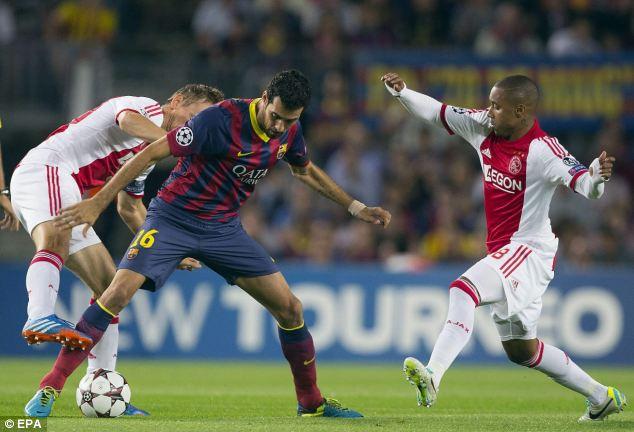 Battle: Sergio Busquets shields the ball from Ajax's Siem de Jong (left) and Lerin Duarte