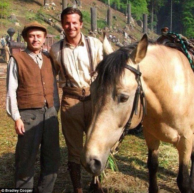 Horse play: Bradley Cooper shared a snap of himself posing with a fellow actor and an equine co-star on the set of Serena on Wednesday